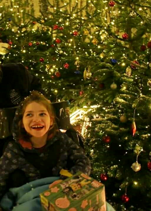 Mya smiling in front of Christmas tree
